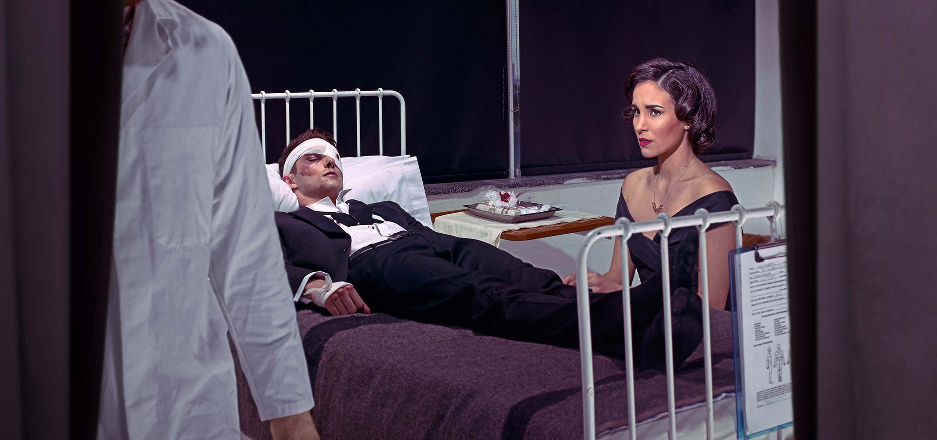 Hospital scene. Man on a bed in a tuxedo with bandage on head. Worried partner looks on.