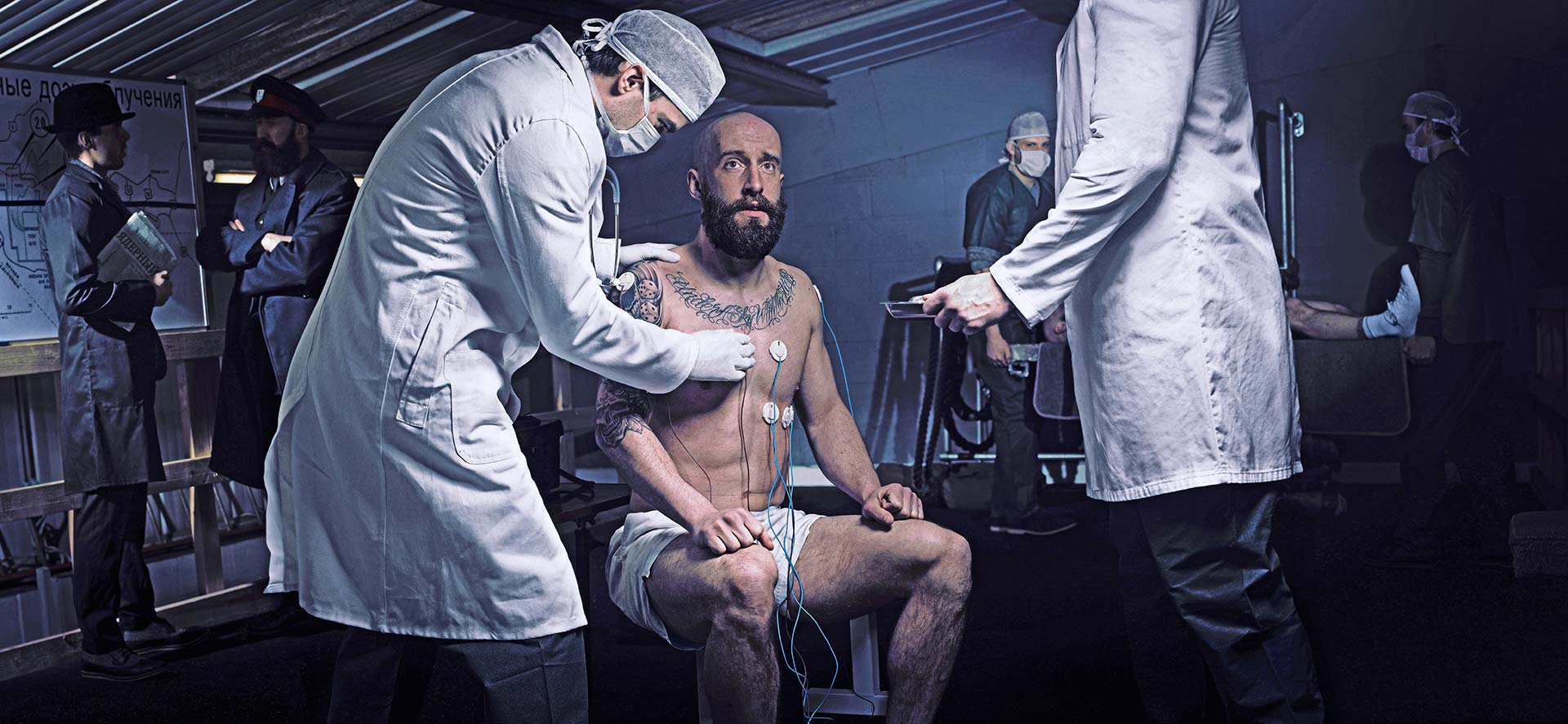 Shirtless bearded man has medical instruments attached to him while doctors and military figures are seen suspiciously in the backgound.