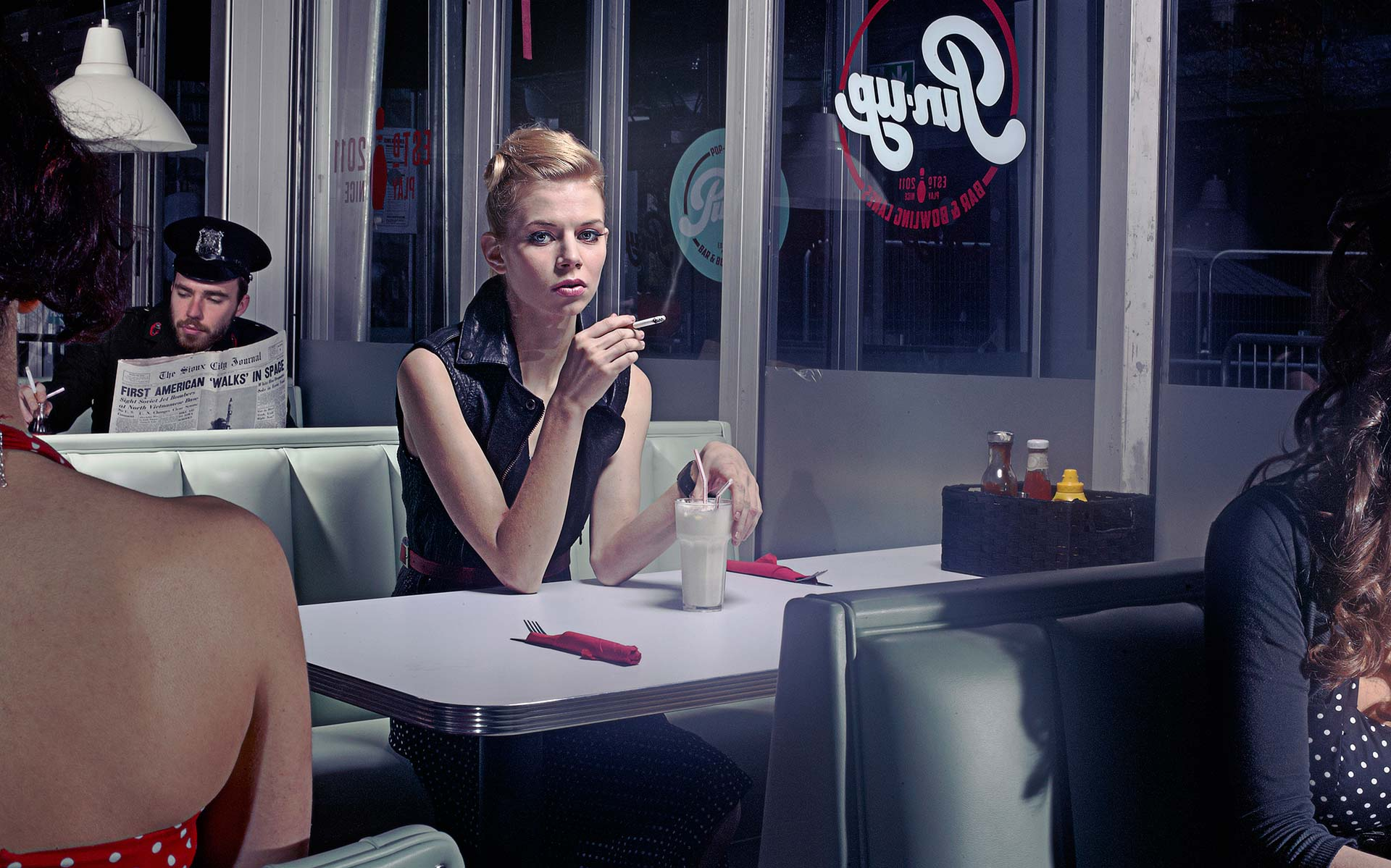 Lone blond female sits waiting for company at a table in an American 1950's Diner. Smoking.